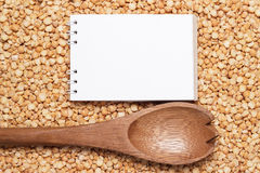 Notebook and wooden spoon over peas background Royalty Free Stock Photos