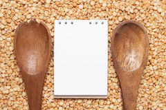 Notebook and wooden spoons over peas background Stock Photography