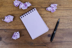Notebook on wooden table with pen on side crumpled paper Stock Photos