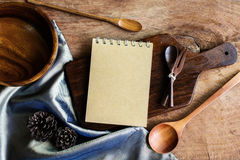 Notebook and wooden utensil in kitchen on old wooden background Stock Images