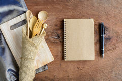 Notebook and wooden utensil in kitchen on old wooden background Stock Photo