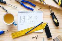 Notebook with the word repair, a mug of tea and tools for building a house or apartment repair, on a wooden table. The workplace stock photo