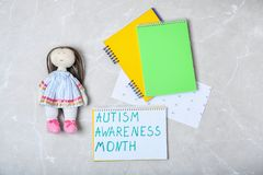 Notebook with words AUTISM AWARENESS MONTH. And doll on grey background, top view Royalty Free Stock Photography