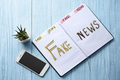 Notebook with words FAKE NEWS and mobile phone on wooden background stock image