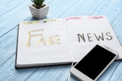 Notebook with words FAKE NEWS and mobile phone on wooden background stock photos