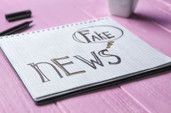 Notebook with words FAKE NEWS on wooden background stock image