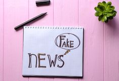 Notebook with words FAKE NEWS on wooden background royalty free stock photo