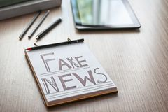 Notebook with words FAKE NEWS on wooden table royalty free stock image