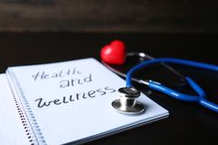 Notebook with words \'Health and wellness\' and medical stethoscope on table, closeup royalty free stock image