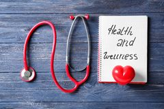 Notebook with words \'Health and wellness\' and medical stethoscope on wooden background royalty free stock photo