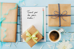 Notebook with the words Thank you for your order, pencil and gift or present box packed in kraft paper on blue wooden table Royalty Free Stock Photos