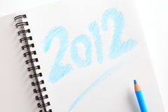 Notebook ( writed 2012) and blue pencil Stock Images