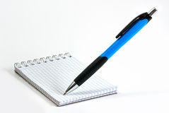 Notebook with writing ballpen. Blue ballpen on small notebook, isolated on white background Royalty Free Stock Photography
