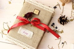 Notebook for writing dreams and memories decorated with bright red ribbon and cute dry rose. Romantic concept Stock Images