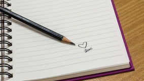 Notebook. Written love and heart in notebook Stock Photography
