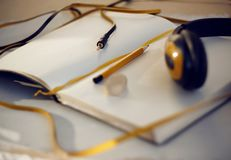 Notebook with yellow bookmark, pencil and headphones stock photography