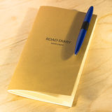 Notebook and pen on yellow table. Notebook with yellow paper and blue pen on yellow table Royalty Free Stock Images