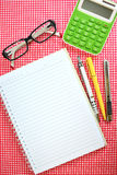 Notebook, yellow pen, gray pencil, green calculator, cutter knife. Royalty Free Stock Photo
