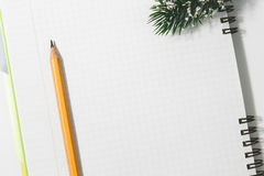 Notebook and yellow pencil with conifer branch on a white backgr. Ound royalty free stock image