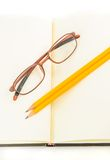 Notebook and yellow pencil and eyeglass Stock Photos