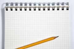 Notebook and yellow pencil on a white background Stock Photography