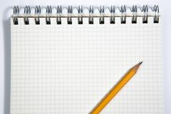 Notebook and yellow pencil on a white background Stock Images