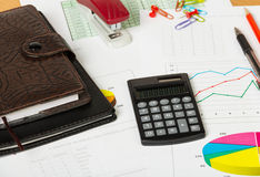 Notebooks, calculator and various stationery items on desktop background. Stock Photos