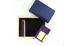 Notebooks, colored pencils, black board. Office tools on white background Stock Images