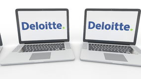 Notebooks with Deloitte logo on the screen. Computer technology conceptual editorial 4K clip, seamless loop. Notebooks with Deloitte logo on the screen. Computer stock video footage
