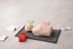 Notebooks, first aid mannequin and bag. On floor indoors royalty free stock photo