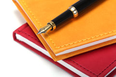 Notebooks and fountain pen. On white background Royalty Free Stock Photo