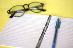 Notebooks, glasses and pens placed on a yellow background Working concept royalty free stock photos