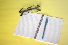 Notebooks, glasses and pens placed on a yellow background Working concept stock images
