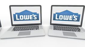 Notebooks with Lowe`s logo on the screen. Computer technology conceptual editorial 4K clip, seamless loop. Notebooks with Lowe`s logo on the screen. Computer stock video footage