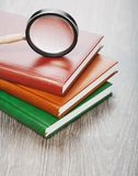 Notebooks and magnifier on wooden background Royalty Free Stock Photo