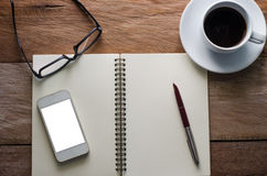 Notebooks, mugs, glasses on a wooden desk. Notebooks, mugs, glasses on a wooden desk Stock Images