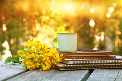 notebooks next to field flowers on wooden table outdoors Royalty Free Stock Photos