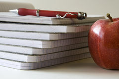 Notebooks with pen and apple Stock Photography