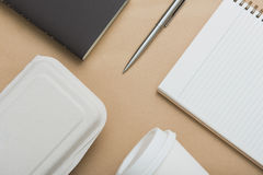 Notebooks, pen, coffee cup and food box on brown paper Royalty Free Stock Images