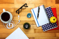 Notebooks, pen, glasses, apple on a wooden Royalty Free Stock Images