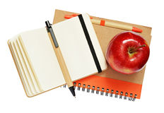 Notebooks, pens and apple Stock Photo
