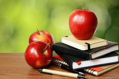 Notebooks, pens and apples on a table Royalty Free Stock Image
