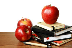 Notebooks, pens and apples on a table Stock Images