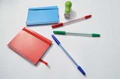 Notebooks, pens, a stapler Royalty Free Stock Photo