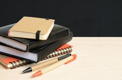 Notebooks and pens on wooden table with school black board stock photos