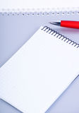 Notebooks with red pen. A red pen on a notebook, isolated in white background Royalty Free Stock Photo