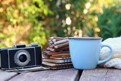 Notebooks, vintage photo camera, colorful pencils. Image of notebooks, vintage photo camera, colorful pencils on wooden table outdoors at afternoon. selective Royalty Free Stock Photos