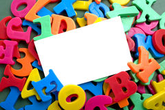 Notecard with Alphabet Letters. A blank white notecard surrounded by brightly colored plastic alphabet letter magnets with copy space Royalty Free Stock Photos