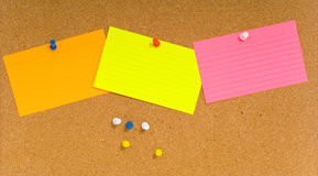 Notecard on corkboard. Bright, blank neon colored notecards on brown corkboard or bulletin board with plastic pushpins, space for copy Stock Image