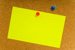 Notecard on corkboard. Bright, blank neon colored notecards on brown corkboard or bulletin board with plastic pushpins, space for copy Royalty Free Stock Photography